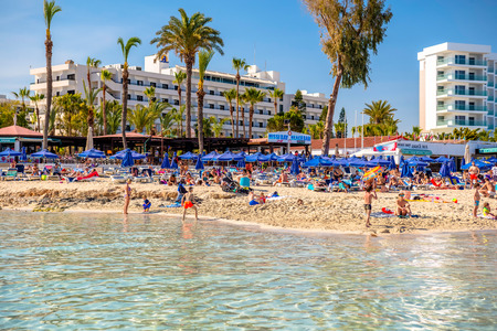 napa: AYIA NAPA, CYPRUS - April 04, 2016: People swimming and sunbathing on the picturesque Nissi beach.