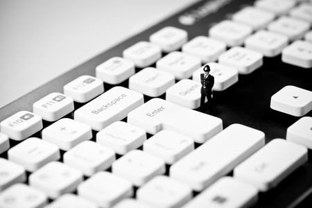criminality: Miniature Police officer on top of computer keyboard. Internet piracy and criminality cpncept. Stock Photo