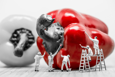 human figures: Miniature painters coloring bell pepper. Macro photo. Stock Photo
