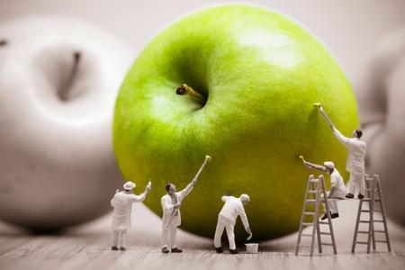 Painters coloring green apple. Macro photo.