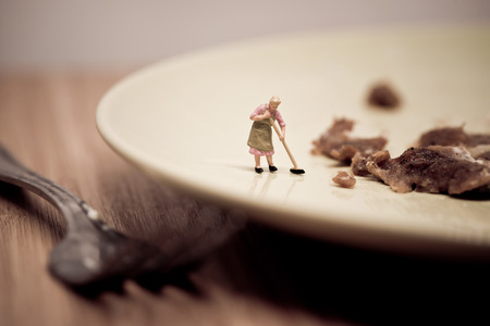 cute house: Miniature housewife washing dirty dish. Macro photo. Stock Photo