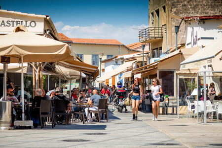 LIMASSOL, CYPRUS - April 01, 2016: People sitting at outdoors restaurant at the Castle Square of Limassol. It is popular touristic place, with plenty of restaurants, stores and bars.