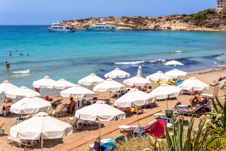the bay: PAPHOS, CYPRUS - JULY 24, 2016: Tourists, sunbeds and umbrellas on hot summer day at Coral Bay Beach.