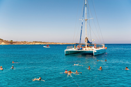 Catamaran loaded with tourists with blue sky and azure water on background Editorial