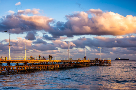 beachfront: Unidentified people walking the pier on a winter day. Limassol, Cyprus. Stock Photo
