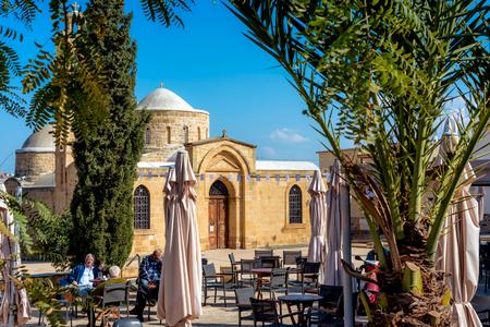PERISTERONA, CYPRUS - MARCH 03, 2017: People sitting at outdoors cafe near Apostles Varnavas Church.