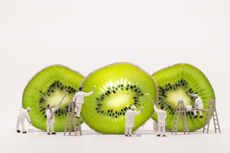 Miniature painters coloring Kiwi slices. Macro photo.