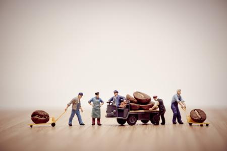 Miniaturarbeiter laden Kaffeebohnen auf LKW. Lizenzfreie Bilder