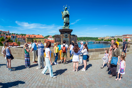 PRAGUE, CZECH REPUBLIC - MAY 28, 2017: Tourists touching a bronze plaque for luck on the St John of Nepomuk statue at Charles bridge.