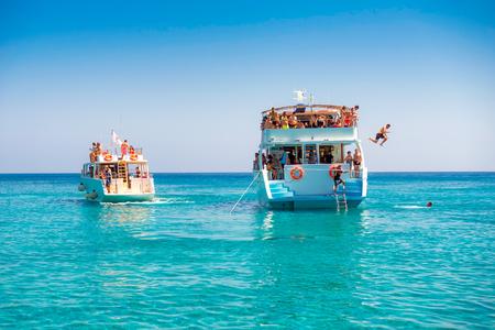 Die Leute springend von einem touristischen Kreuzfahrtboot in das Mittelmeer. Zypern.