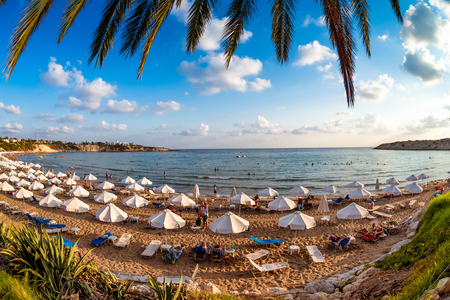 Tourists relaxing on the beach in the summer vacation. Peyia village, Paphos District, Cyprus.