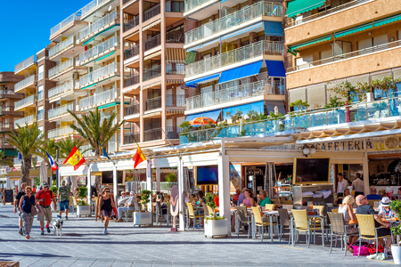 TORREVIEJA, SPAIN - NOVEMBER 13, 2017: Seafront promenade de los Marineros with restaurants and cafes on a sunny day.