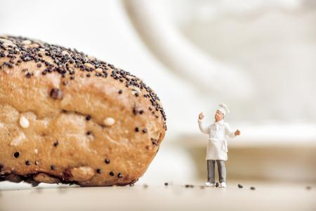 ?heerful baker standing near bun with poppy seeds.