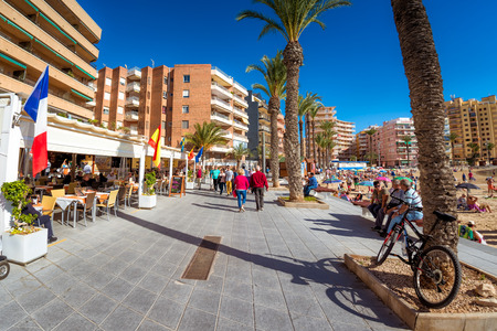 TORREVIEJA , SPAIN - NOVEMBER 13, 2017: people walk on promenade at de los Marineros avenue with tourist shops cafes and restaurants. Editorial