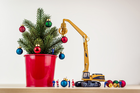Miniature workers decorating christmas tree.