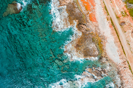 Overhead view of turquoise sea, waves and a rocky shoreline