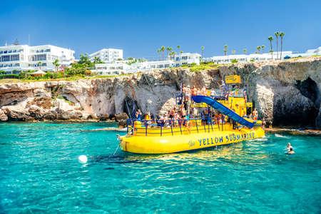 AYIA NAPA, CYPRUS - August 10, 2019: Recreational boat with tourists near the rocky cliffs near Ayia Napa. Famagusta District, Cyprus Sajtókép