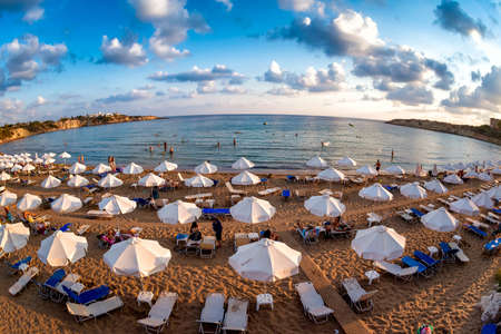 Rows of beach lounges and sun umbrellas on a Coral Bay beach near Peyia village. Standard-Bild