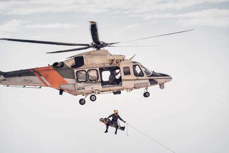 Search and rescue SAR helicopter team hoists an injured person Standard-Bild