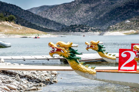 Dragon boats moored at wooden pier or jetty on the lake Standard-Bild