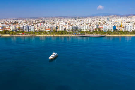 Yacht cruising near Limassol seafront, aerial view