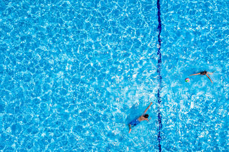 Kids playing with a ball in a swimming pool. Overhead view