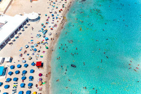 Aerial view Nissi bay beach. People, umbrellas, sand and sea wave. Famagusta District, cyprus