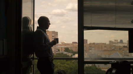 man in office standing in the window and drink