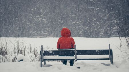a girl in a red jacket with a hood sits alone, in winter on park benches Stok Fotoğraf