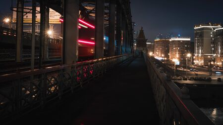 pedestrian railway bridge and the lights of a passing train at night