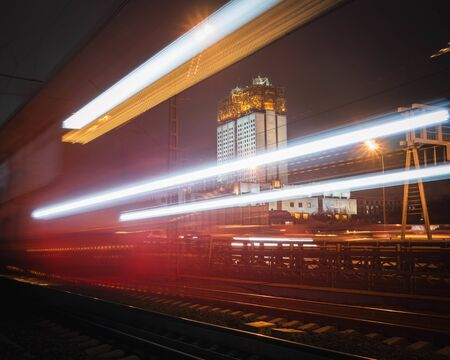 Blurry lights of a passing train. High building in the background. Stok Fotoğraf