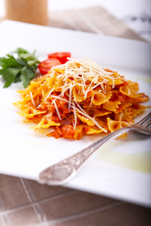 Farfalle pasta with sauce and cheese, served on a white plate. Farfalle Paste In appearance they resemble bows or butterflies.