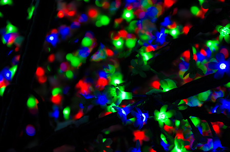 multicolored christmas light bulb leaves with blurred background