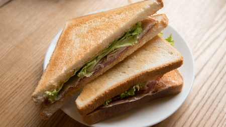 cooked sandwich with salami and lettuce leaves. Fast snack for an office worker