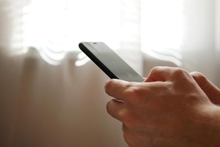 black smartphone in hands close-up