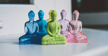 multicolored plastic buddha figurines on a light background. Modern Religions in the World