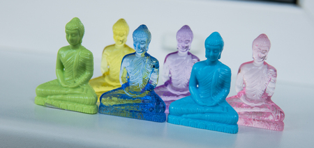 multicolored plastic buddha figurines on a light background. Modern Religions in the World Stock Photo - 114215733