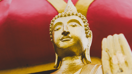 a statue of a golden buddha close-up. Bodhi condition of holy god