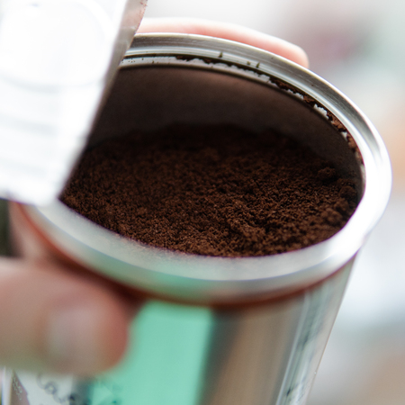 ground coffee from a metal can. Making morning coffee