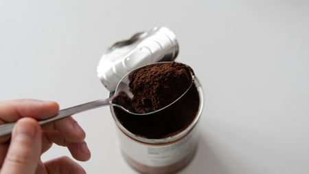 ground coffee in a tablespoon. Portion of coffee for cooking.