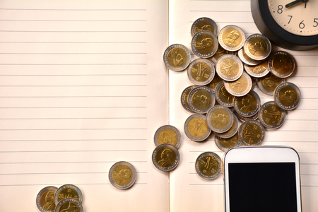 Coins, smart phone and clock put on notebook.