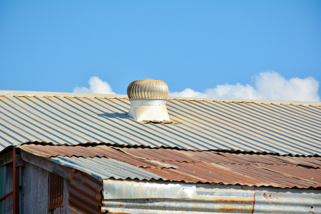 Rusty roofing iron and ventilated roof under the blue sky