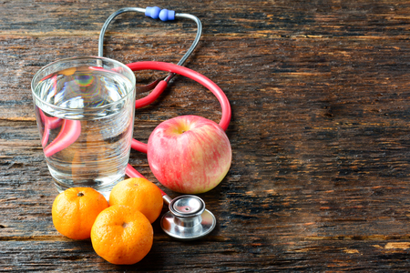 Tools doctor a stethoscope behind an apple, oranges and water glass for healthy put on wood table Stock Photo