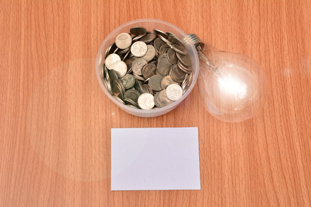 White paper mock up,light bulb for idea and stack coins in glass put on hand for save money and financial, tax season Stock Photo