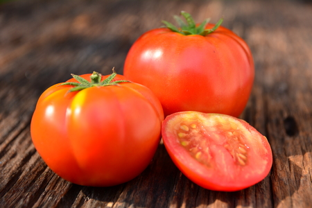 Fresh red tomato on old brown wood table at the morning