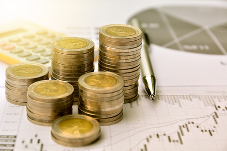 money coins with graph paper and calculator, finance and growth of business Stock Photo