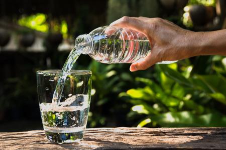 Mano femenina que vierte agua de la botella al vidrio en el fondo de la naturaleza Foto de archivo - 78307259