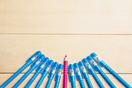 old items: pens or writing tools on wooden table and red pen middle among blue top view Stock Photo