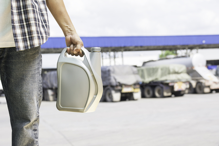 Hand of male holing gray plastic canister of motor oil on gas station background