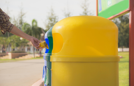 paperless: blue and yellow plastic trashcan in the park at summer. Colored trash containers. Stock Photo